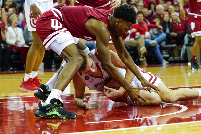 Wisconsin's Tyler Wahl, bottom, and Indiana's Aljami Durham (1) battle for a loose ball during the second half of an NCAA college basketball game Saturday, Dec. 7, 2019, in Madison, Wis. Wisconsin won 84-64. (AP Photo/Andy Manis)
