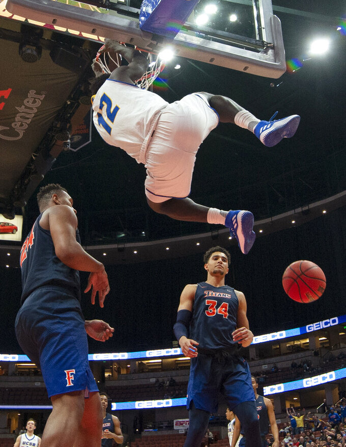 UC Santa Barbara forward Amadou Sow hangs from the rim after a dunk, as Cal State Fullerton forward Josh Pitts, left, and forward Jackson Rowe stand nearby during the first half of an NCAA college basketball game at the Big West men's tournament in Anaheim, Calif., Friday, March 15, 2019. (AP Photo/Kyusung Gong)