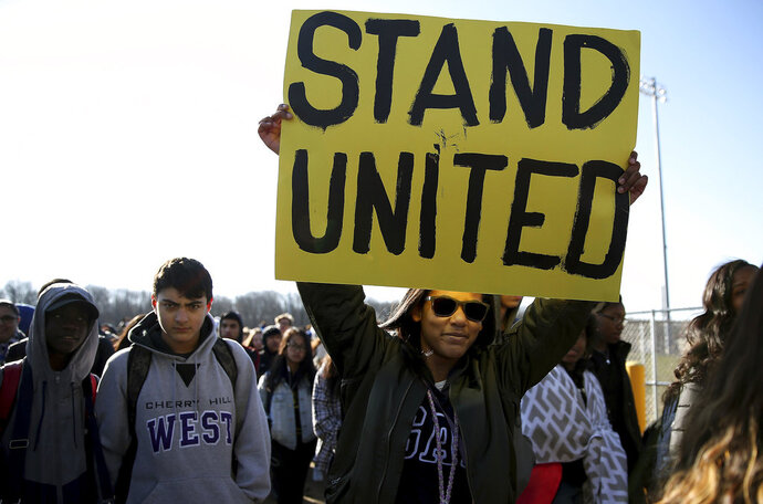 Freshman Kennedi Lawson, 14, carries a sign as student walkout at Cherry Hill West High School in remembrance of those killed in the Parkland, Fla., shooting in Cherry Hill, N.J., on Wednesday, March 14, 2018.  ( David Maialetti  /The Philadelphia Inquirer via AP)
