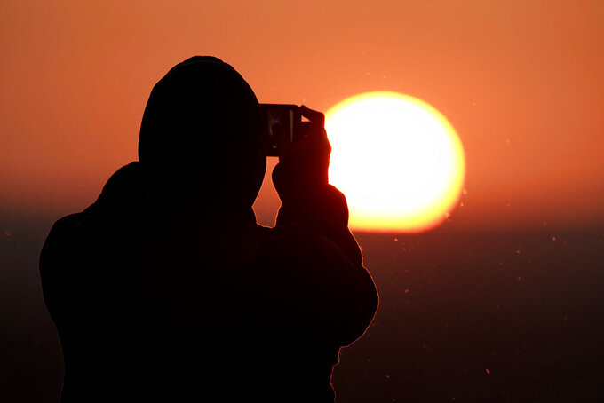 A worker at Arrowhead Stadium takes a photo of the sunset before an NFL football game between the Kansas City Chiefs and Denver Broncos in Kansas City, Mo., Sunday, Dec. 6, 2020. (AP Photo/Charlie Riedel)
