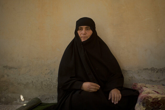In this Saturday, Sept. 7, 2019, photo, Um Mahmoud recalls her experience returning to Raqqa, Syria, during an interview in the courtyard of her home. After two years on the run with the Islamic State group, Um Mahmoud was ready to return home. In June, she finally made it back to Raqqa with her three daughters and three grandchildren -- finding an empty, partially burned house and a hostile city. (AP Photo/Maya Alleruzzo)