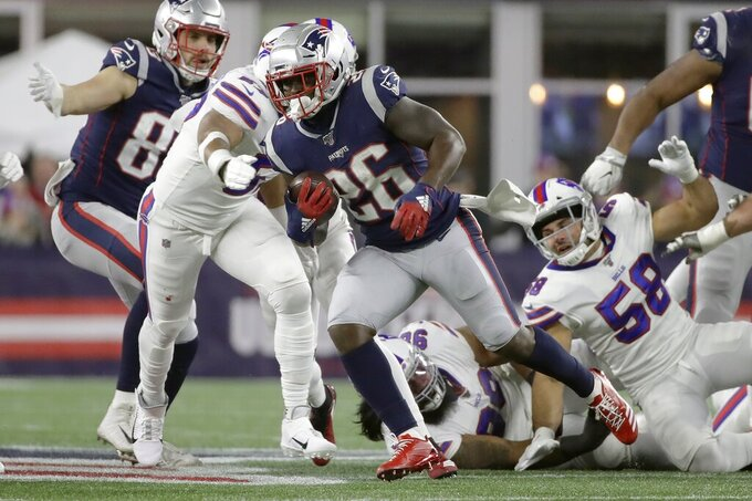 New England Patriots running back Sony Michel (26) runs away from Buffalo Bills linebacker Matt Milano (58) in the first half of an NFL football game, Saturday, Dec. 21, 2019, in Foxborough, Mass. (AP Photo/Elise Amendola)