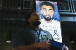 South Carolina artist, Joey Withinarts, stands in front of portraits of Chadwick Boseman dressed as the Black Panther on Thursday, Oct. 22, 2020 in Anderson, S.C. Withinarts started painting his portrait of the hometown star just hours after he heard of his passing in August. (Charles McBryde, Via AP)