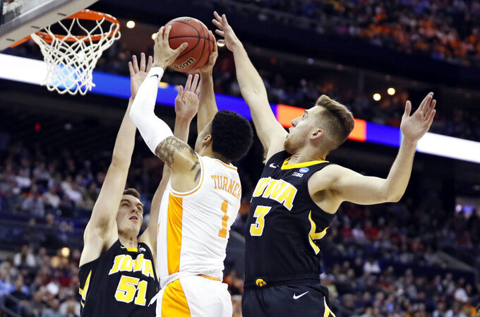 Tennessee's Lamonte Turner (1) drives to the basket between Iowa's Nicholas Baer (51) and Iowa's Jordan Bohannon (3) in the first half during a second-round men's college basketball game in the NCAA Tournament in Columbus, Ohio, Sunday, March 24, 2019. (AP Photo/John Minchillo)