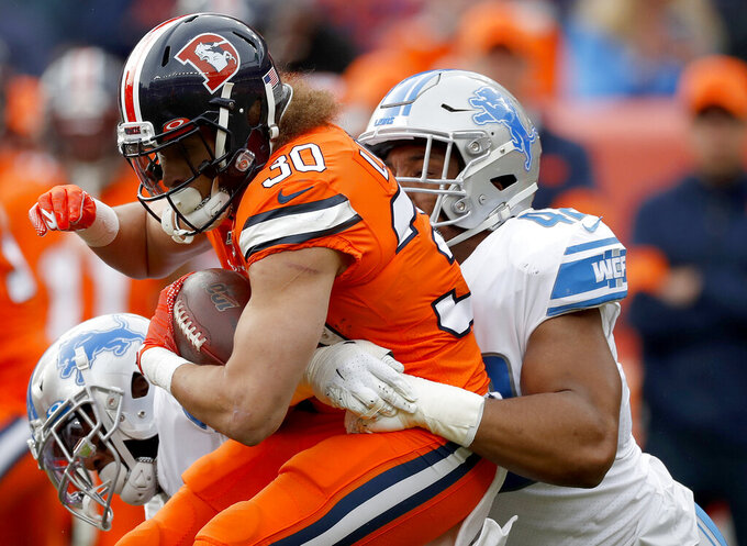 FILE - In this Dec. 22, 2019, file photo, Denver Broncos running back Phillip Lindsay (30) is tackled by Detroit Lions outside linebacker Devon Kennard during the first half of an NFL football game in Denver. Arizona native Kennard is ready to aid the Cardinals' defensive rebuild. The edge rusher had seven sacks in each of the past two seasons with the Detroit Lions and agreed to a three-year deal with the Cardinals on March 15, 2020. (AP Photo/David Zalubowski, File)