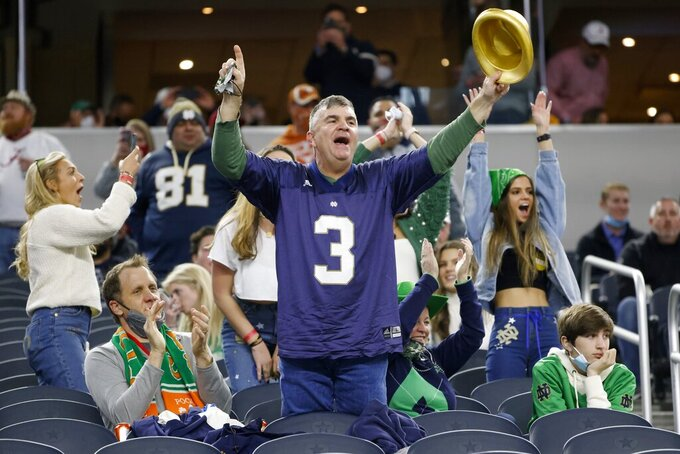 A Notre Dame fan is joined by others as they watch the teams jog onto the field or the the Rose Bowl NCAA college football game against Alabama in Arlington, Texas, Friday, Jan. 1, 2021. (AP Photo/Michael Ainsworth)