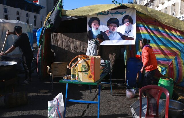 Free food is prepared for protesters during the ongoing anti-government protests next to a poster of Muqtada al-Sadr whose image is centered between the image of his father, Ayatollah Mohammed Sadiq al-Sadr, right, and Shiite spiritual leader Grand Ayatollah Ali al-Sistani, left, in Tahrir Square in Baghdad, Iraq, Saturday, Feb. 1, 2020. Influential and radical cleric Muqtada al-Sadr called for his followers to return to the street, one week after he withdrew support for anti-government demonstrators camped out in Baghdad's Tahrir Square. (AP Photo/Khalid Mohammed)