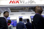 FILE - In this Tuesday, Oct. 23, 2018, file photo, visitors pass by a booth for state-owned surveillance equipment manufacturer Hikvision at the Security China 2018 expo in Beijing, China. The United States is blacklisting a group of Chinese tech companies that develop facial recognition and other artificial intelligence technology that the U.S. says is being used to repress China's Muslim minority groups. The blacklisted companies include Hikvision, a global provider of video surveillance technology. (AP Photo/Ng Han Guan, File)