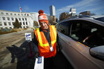 Election judge Adam Ballinger takes a ballot from a voter at the drive-through site of the Denver Election Division outside the City/County Building early Tuesday, Nov. 5, 2019, in Denver. (AP Photo/David Zalubowski)