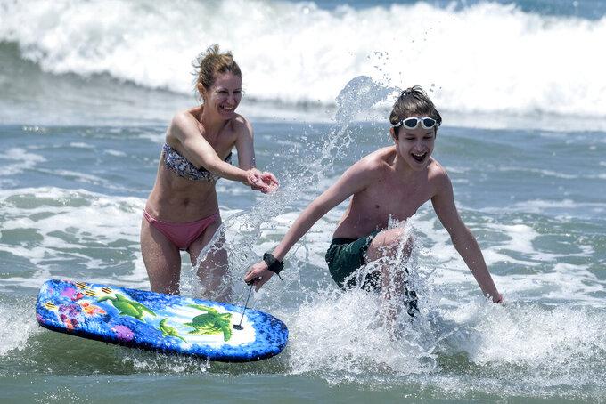 People play in the water at Santa Monica Beach on Wednesday, June 16, 2021, in Santa Monica, Calif. (AP Photo/Ringo H.W. Chiu)