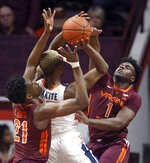 Virginia's Mamadi Diakite (25) has his shot blocked as Virginia Tech's Isaiah Wilkins (1) and John Ojiako (21) defend during the first half of an NCAA college basketball game Wednesday, Feb. 26, 2020, in Blacksburg, Va. (Matt Gentry/The Roanoke Times via AP)