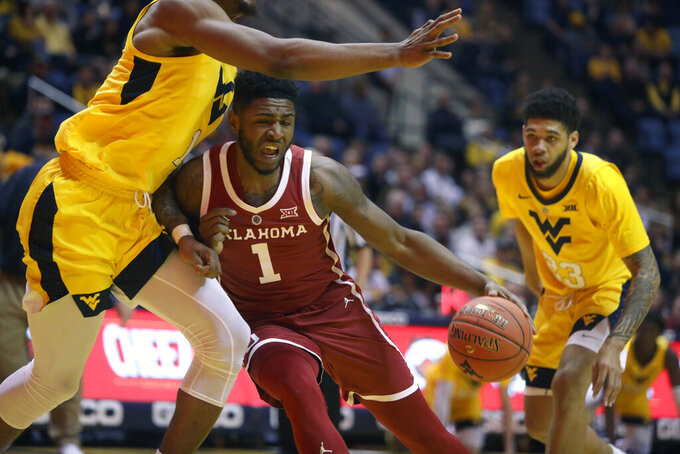 Oklahoma guard Rashard Odomes (1) drives while guarded by West Virginia forward Derek Culver (1) during the first half of an NCAA college basketball game Saturday, Feb. 2, 2019, in Morgantown, W.Va. (AP Photo/Raymond Thompson)