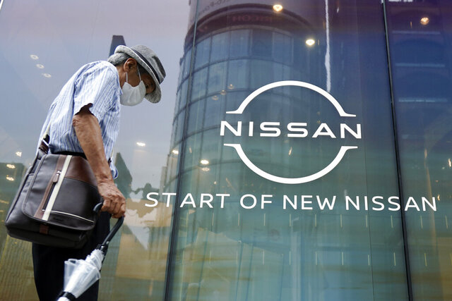 A man walks by new logo of Nissan seen at the automaker's showroom in Tokyo Tuesday, July 28, 2020.  Nissan reported a 285.6 billion yen ($2.7 billion) loss for April-June, as the Japanese automaker sales crashed amid the coronavirus pandemic and it struggled to recover from the loss of its former star executive Carlos Ghosn. (AP Photo/Eugene Hoshiko)