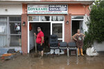 Locals try to move away water and mud from their shop following a storm at the village of Politika, on Evia island, northeast of Athens, on Sunday, Aug. 9, 2020. Five people have been found dead and dozens have been trapped in their homes and cars from a storm that has hit the island of Evia, in central Greece, police say. (AP Photo/Yorgos Karahalis)