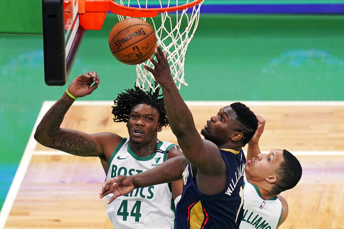 New Orleans Pelicans forward Zion Williamson, center, reaches for a rebound against Boston Celtics center Robert Williams III, left, and forward Grant Williams, right, during the second half of an NBA basketball game, Monday, March 29, 2021, in Boston. (AP Photo/Charles Krupa)