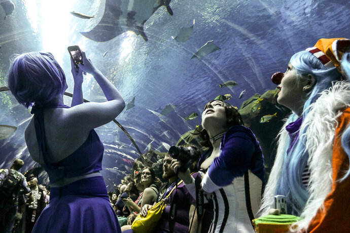 FILE - In this Saturday, Sept. 5, 2015, photo, three women in costumes look at sea life swimming above them during a private party held at the Georgia Aquarium as part of Dragon Con in Atlanta. Officials announced Monday, July 6, 2020 that Dragon Con will be canceled for 2020 in response to the coronavirus pandemic. Dragon Con was originally set to take place over Labor Day weekend. It will instead be moved online for a virtual event. (AP Photo/Ron Harris, File)