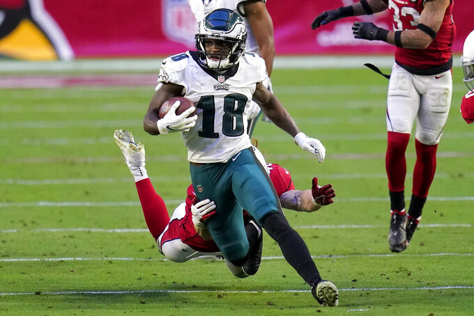 Philadelphia Eagles wide receiver Jalen Reagor (18) eludes the grasp of Arizona Cardinals linebacker Dennis Gardeck during the second half of an NFL football game, Sunday, Dec. 20, 2020, in Glendale, Ariz. (AP Photo/Ross D. Franklin)
