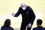 San Antonio Spurs head coach Gregg Popovich in a mask as he talks with players on the bench during the second half of an NBA basketball game against the Houston Rockets Tuesday, Dec. 15, 2020, in Houston. (AP Photo/Michael Wyke)