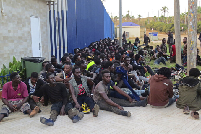 A group of Migrants sit at a migrant processing center in Melilla, Spain, July 22, 2021. Authorities in Spain's autonomous city of Melilla say that 238 African men have made it to the Northern African Spanish enclave after climbing over fences separating it from Morocco. Sub-Saharan migrants fleeing poverty or violence regularly attempt to trespass the 12-kilometer-long (7.4-miles) border in Melilla and in Spain's other enclave in the northern African coast, Ceuta, as a stepping stone to reach the European continent. (Europa Press via AP)