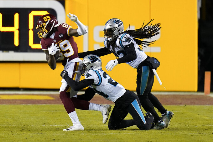 Washington Football Team wide receiver Cam Sims (89) is taken down by Carolina Panthers cornerback Rasul Douglas (24) and Carolina Panthers free safety Tre Boston (33) during the second half of an NFL football game, Sunday, Dec. 27, 2020, in Landover, Md. (AP Photo/Carolyn Kaster)