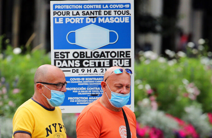 People wearing face masks to protect against coronavirus walk past a sign stating face coverings are required in the street, in Bayonne, southwestern France, Wednesday, July 28, 2021. Local authorities in France are re-imposing mask mandates and other virus restrictions because of fast-growing infections with the delta variant, which is causing COVID-19 hospitalizations in France to rise again. (AP Photo/Bob Edme)