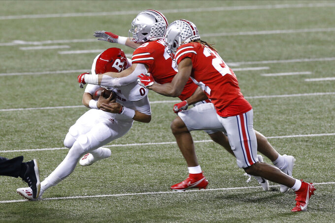 Ohio State linebacker Pete Werner, center, and defensive back Shaun Wade, right, tackle Rutgers quarterback Noah Vedral during the first half of an NCAA college football game Saturday, Nov. 7, 2020, in Columbus, Ohio. (AP Photo/Jay LaPrete)