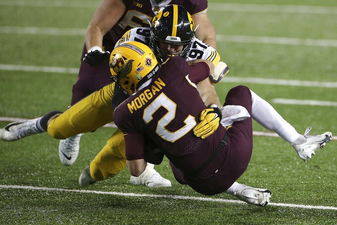 Iowa defensive lineman Zach VanValkenburg (97) sacks Minnesota quarterback Tanner Morgan (2) during the second half of an NCAA college football game Friday, Nov. 13, 2020, in Minneapolis. Iowa won 35-7. (AP Photo/Stacy Bengs)