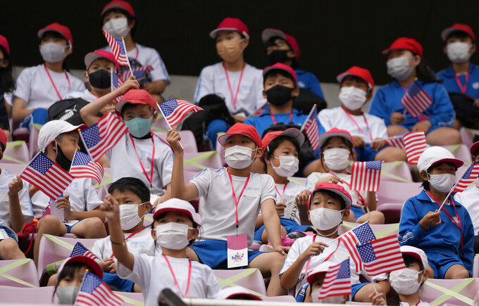 School kids hold U.S. flags as they wait a women's soccer match between United States and Australia at the 2020 Summer Olympics, Tuesday, July 27, 2021, in Kashima, Japan. (AP Photo/Fernando Vergara)