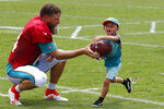 Miami Dolphins quarterback Ryan Fitzpatrick, hands off to Koa Walton, 3, of Port St. Lucie, Fla., after the teams NFL football training camp, Tuesday, July 30, 2019 in Davie, Fla. (AP Photo/Wilfredo Lee)