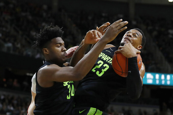 Michigan State forward Xavier Tillman (23) grabs a rebound next to teammate Julius Marble (34) during the first half of an NCAA college basketball game against Wisconsin, Friday, Jan. 17, 2020, in East Lansing, Mich. (AP Photo/Carlos Osorio)