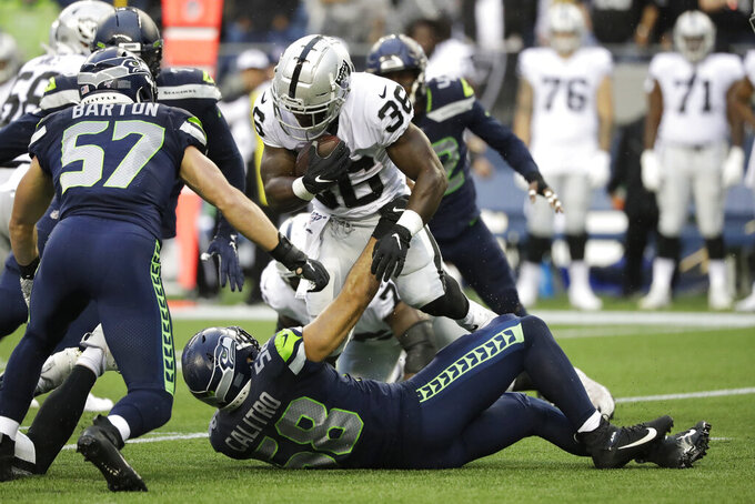Oakland Raiders running back James Butler (36) is tackled by Seattle Seahawks outside linebacker Austin Calitro (58) during the first half of an NFL football preseason game Thursday, Aug. 29, 2019, in Seattle. (AP Photo/Elaine Thompson)