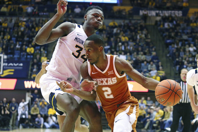 Texas guard Matt Coleman III (2) is defended by West Virginia forward Oscar Tshiebwe (34) as he goes to pass the ball during the first half of an NCAA college basketball game Monday, Jan. 20, 2020, in Morgantown, W.Va. (AP Photo/Kathleen Batten)