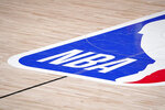 FILE - In this Sept. 2, 2020, file photo, the NBA logo is displayed at center court during an NBA first-round playoff basketball game between the Houston Rockets and Oklahoma City Thunder in Lake Buena Vista, Fla. NBA training camps open around the league Tuesday, Dec. 1, 2020,though on-court sessions will be limited to individual workouts and only for those players who have gotten three negative coronavirus test results back in the last few days. (AP Photo/Mark J. Terrill, File)