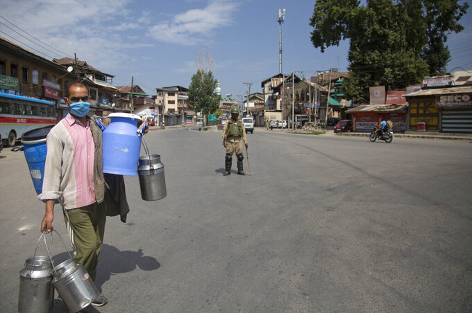 """A Kashmiri milkman walks past a paramilitary soldier during curfew in Srinagar, Indian controlled Kashmir, Tuesday, Aug. 4, 2020. Authorities clamped a curfew in many parts of Indian-controlled Kashmir on Tuesday, a day ahead of the first anniversary of India's controversial decision to revoke the disputed region's semi-autonomy. Shahid Iqbal Choudhary, a civil administrator, said the security lockdown was clamped in the region's main city of Srinagar in view of information about protests planned by anti-India groups to mark Aug. 5 as """"black day."""" (AP Photo/Mukhtar Khan)"""