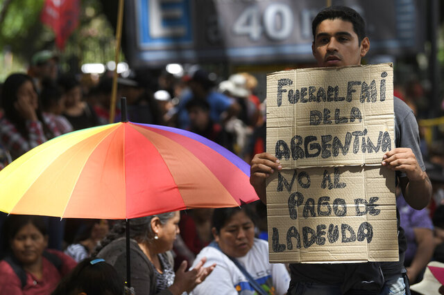 Members of political parties and social movements protest the visit of an International Monetary Fund (IMF) delegation, one with a sign that reads in Spanish