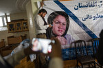 """A man holds a poster of Afghan politician Fawzia Koofi prior to a press conference organized by the """"movement of change for Afghanistan Party"""" in Kabul, Afghanistan, Sunday, Sept. 19, 2021. (AP Photo/Bernat Armangue)"""