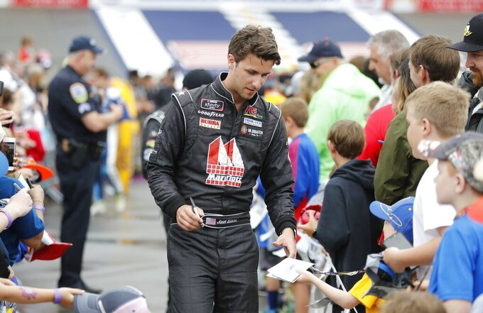 Josh Bilicki signs autographs before the NASCAR cup series auto race at Michigan International Speedway, Sunday, June 9, 2019, in Brooklyn, Mich. (AP Photo/Carlos Osorio)