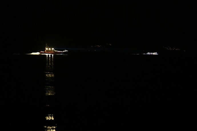 A patrol boat uses a light to spot a dinghy with refugees and migrants between Turkey and Skala Sykaminias village, on the northeastern Aegean island of Lesbos, Greece, Tuesday, Sept. 24, 2019. More than 2,300 migrants reached Lesbos last week, the highest rate of arrival this year. (AP Photo/Michael Varaklas)