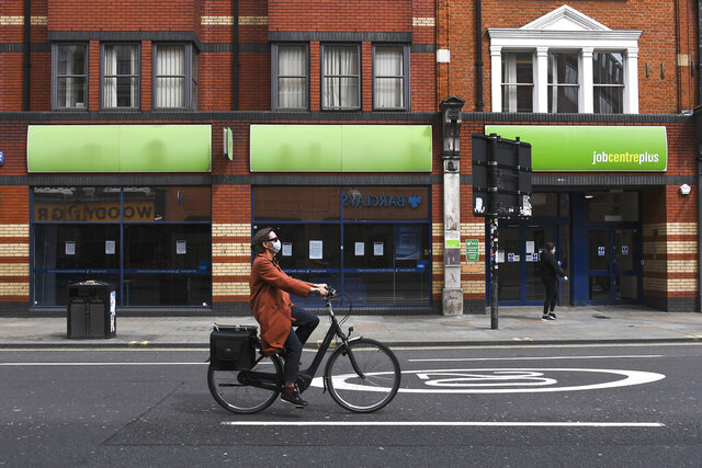 FILE - In this Thursday, April 30, 2020 file photo, a woman wearing a mask to protect against coronavirus, rides a bicycle past a job centre in Shepherd's Bush, as the lockdown to curb the spread of coronavirus continues, in London. The U.K. economy has officially fallen into a recession after official figures showed it contracting by a record 20.4% in the second quarter as a result of lockdown measures put in place to counter the coronavirus pandemic. The slump recorded by the Office for National Statistics follows a 2.2% quarterly contraction in the first three months of the year.  (AP Photo/Alberto Pezzali, File)