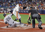 Home plate umpire Cory Blaser, right, watches as New York Yankees' DJ LeMahieu (26) scores on a passed ball, as pitcher Tyler Glasnow, center, covers the plate during the first inning of a baseball game Friday, May 10, 2019, in St. Petersburg, Fla. (AP Photo/Steve Nesius)