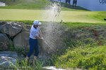 Bo Hoag hits while standing ankle-deep in water on the 18th hole during the third round of the 3M Open golf tournament in Blaine, Minn., Saturday, July 24, 2021. (AP Photo/Craig Lassig)