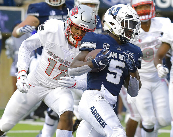 Utah State running back Darwin Thompson (5) carries the ball for a 7-yard touchdown, next to UNLV defensive back Evan Austrie (17) during an NCAA college football game Saturday, Oct. 13, 2018, in Logan, Utah. (Eli Lucero/The Herald Journal via AP)