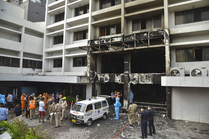 Rescuers and others stand outside Hotel Swarna Palace where a fire broke out early morning in Vijayawada, Andhra Pradesh state, India, Sunday, Aug. 9, 2020. The fire in the hotel being used as a COVID-19 facility killed seven coronavirus patients. (AP Photo)