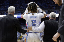 North Carolina guard Cole Anthony (2) is assisted by head coach Roy Williams, left, following an injury during the first half of an NCAA college basketball game against Ohio State in Chapel Hill, N.C., Wednesday, Dec. 4, 2019. (AP Photo/Gerry Broome)