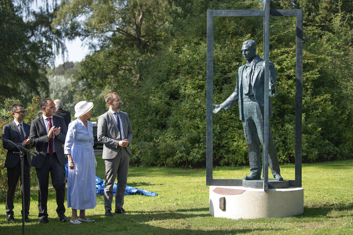 Denmark's Queen Margrethe unveils a statue of Bernhard Sindberg in Memorial Park, Aarhus, Denmark, Saturday Aug. 31, 2019. The Queem unveiled a statue of Bernhard Sindberg, a Dane who is credited with rescuing thousands of Chinese people in December 1937 when Imperial Japanese troops invaded Nanjing, the capital of China at the time. (Bo Amstrup/Ritzau Scanpix via AP)
