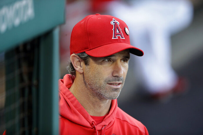FILE - In this Aug. 15, 2019, file photo, Los Angeles Angels manager Brad Ausmus watches from the dugout during the team's baseball game against the Chicago White Sox, in Anaheim, Calif. Manager Brad Ausmus has been fired by the Los Angeles Angels after just one season in charge. Angels general manager Billy Eppler announced the decision to move on swiftly from Ausmus on Monday, Sept. 30, 2019, a day after they finished 72-90 for the franchise's worst record since 1999. (AP Photo/Marcio Jose Sanchez, File)