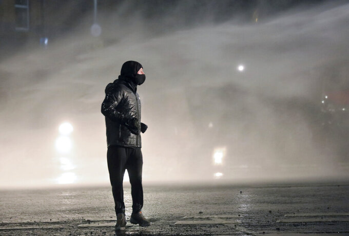 A Nationalist youth is soaked by a police water cannon near the Peace Wall in West Belfast, Northern Ireland, Thursday, April 8, 2021. Authorities in Northern Ireland sought to restore calm Thursday after Protestant and Catholic youths in Belfast hurled bricks, fireworks and gasoline bombs at police and each other. It was the worst mayhem in a week of street violence in the region, where Britain's exit from the European Union has unsettled an uneasy political balance. (AP Photo/Peter Morrison)