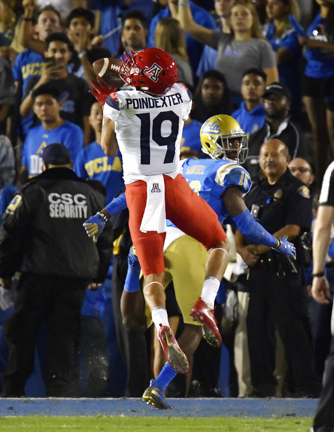 Arizona wide receiver Shawn Poindexter, left, makes a touchdown catch as UCLA defensive back Colin Samuel defends during the first half of an NCAA college football game, Saturday, Oct. 20, 2018, in Pasadena, Calif. (AP Photo/Mark J. Terrill)
