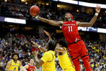 Texas Tech forward Tariq Owens (11) shoots over Michigan defenders during the second half an NCAA men's college basketball tournament West Region semifinal Thursday, March 28, 2019, in Anaheim, Calif. (AP Photo/Marcio Jose Sanchez)
