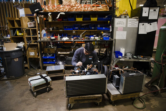 FILE - In this Oct. 18, 2018, file photo Minh Pham works on a compressor unit at a commercial refrigeration manufacturing facility in Philadelphia. Small manufacturers and retailers are losing confidence in the national economy yet remain upbeat about their own prospects. That's the finding of a third quarter survey of 1,000 companies released last week by the U.S. Chamber of Commerce and MetLife. (AP Photo/Matt Rourke, File)
